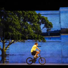 A young man wearing a yellow t-shirt rides a bicycle on a theatre stage.