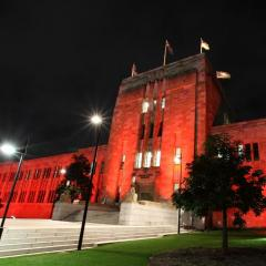 Forgan Smith Building at UQ St Lucia lit by red lights at night.