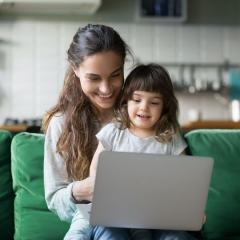 Happy laughing mother and preschool daughter using laptop together on a green couch.
