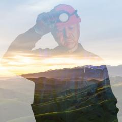A miner overlaid over a scenic background.
