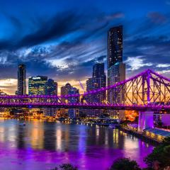 An image of Brisbane and the Story Bridge lit up at night time.