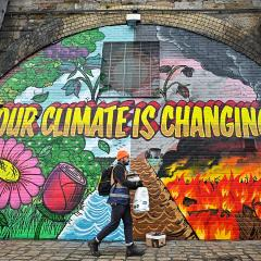 A man walks past a mural in Glasgow, which says 'Our climate is changing'.