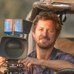 An image of Dr Chadden Hunter sitting in a jeep with a video camera attached to it.