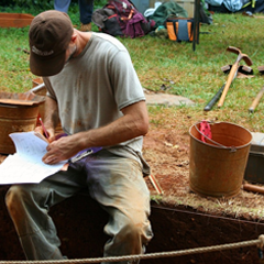 Man taking notes at an archaeological dig