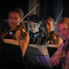 Four violinists playing in a dark room