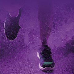 Feet in running shoes with purple powder background