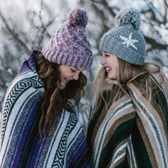 Two white women dressed in warm cltothes, standing in the snow and they are laughing