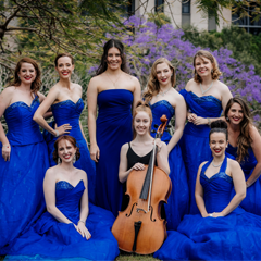 Eight women dressed in blue owns one holds a cello