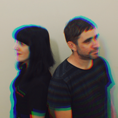A man and a woman stand against a white wall, they are looking off into the distance