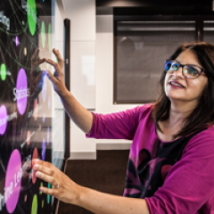 woman with dark hair and glasses looks at a touchscreen board