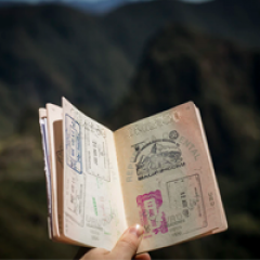 Hand holding an open passport with lots of stamps, mountians in background