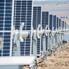 Rows of solar panels in a sandy, flat landscape.