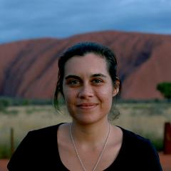 An image of Indigenous journalist and UQ PhD student Amy McQuire in front of Uluru