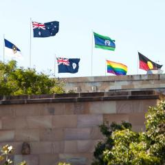 An image An image of the rainbow pride flag flying above the Forgan Smith tower at UQ.