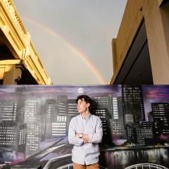 An image of UQ Doctor of Medicine student and The VacSeen Project co-director Jeremy Hunt standing in front of a cityscape mural in Brisbane. A rainbow is beaming through stormy skies in the background..