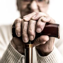 An image of an old ladies hands clasping a walking stick. The image contains a headline, which says, 'a broken system'.