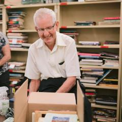 An image of Book group volunteer Robert Bourke sorting through books..