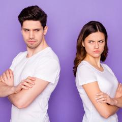 An image of an couple standing back-to-back looking annoyed.