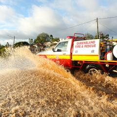 An image of a fire and rescue vehicle driving through floodwater
