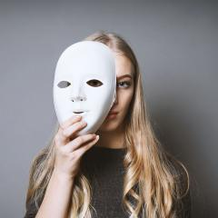 An image of a woman holding a mask partly covering her face