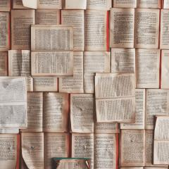 Old books laid out on top of each other with the pages open to create a carpet of mismatched pages.