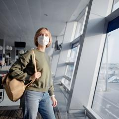 An image of a young woman with a backpack and wearing a face mask while waiting for her plane at an airport.