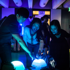 Three young people looking at, and pointing at a blue light